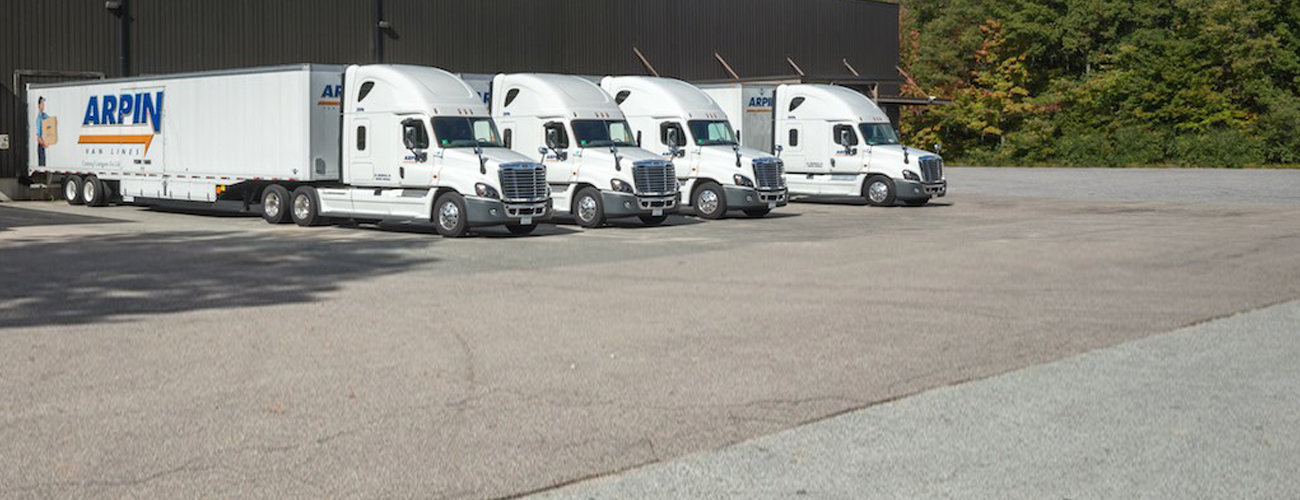 4 Arpin trucks parked outside a buidling