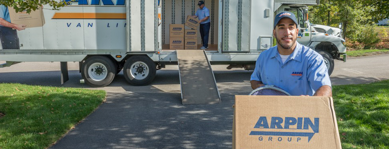 Two men moving boxes off of an Arpin truck